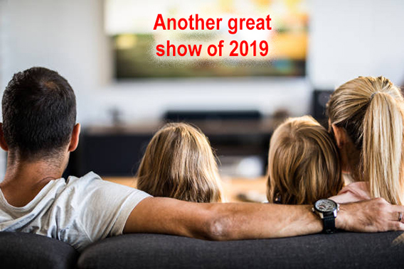 Rear view of a family watching TV on sofa at home.